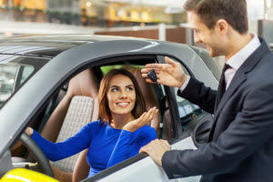 Woman-in-drivers-seat-man-handing-her-keys-chrysler-dealer-dick-huvaeres-richmond-chrysler-dodge-jeep-ram-richmond-mi
